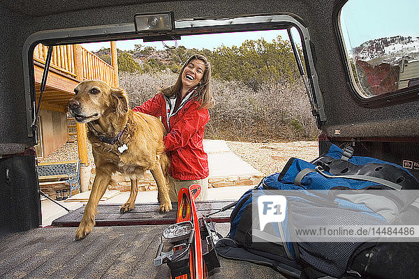 Woman loads Golden Retriever into back of vehicle. Winter