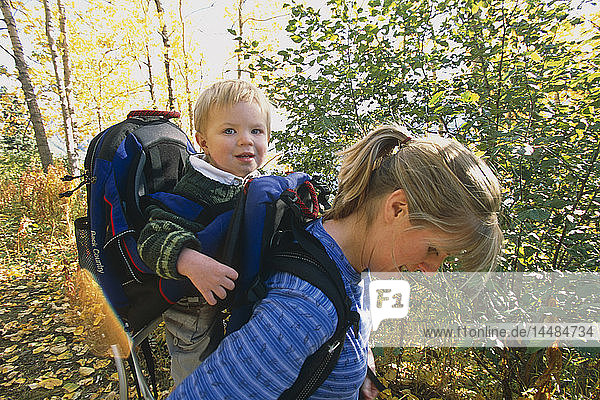 Mother carrying son in backpack on hike Chugach State Park Eagle River Valley Southcentral AK Fall