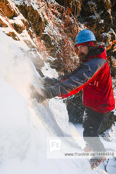 Man gets sprayed with ice as he free climbs a small waterfall near Rainbow Fall  Tongass National Forest  Wrangell Island  Southeast Alaska  Winter
