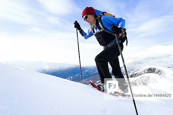 Woman snowshoeing high on ridge above Eagle River in Chugach State Park. Winter in Southcentral Alaska.