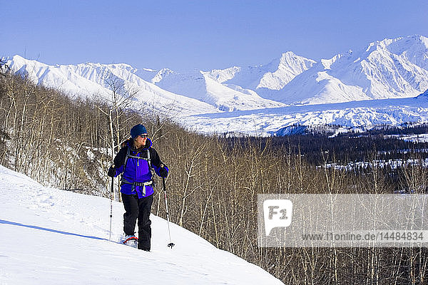 A Woman enjoys a sunny day of snowshoeing in the Talkeetna Mountains near the Matanuska Glacier. Winter in Southcentral Alaska.