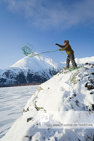 Mountain climber stands near the top of a cliff above the frozen surface of Portage Lake in the Chugach National Forest. Winter in Southcentral Alaska.