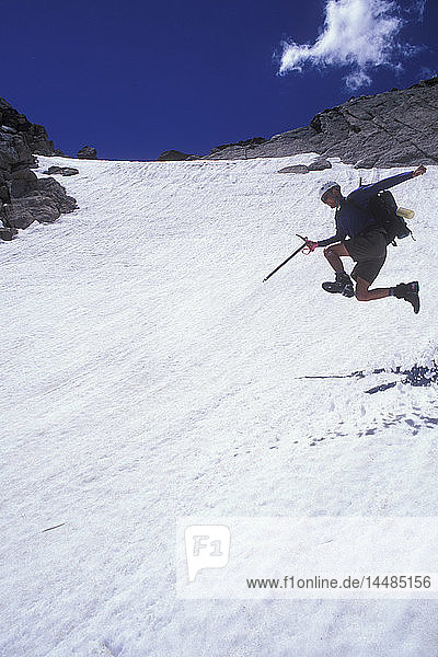 Hiker with an ice axe jumping down a mountain snowfield  Rocky Mountain National Park  Colorado