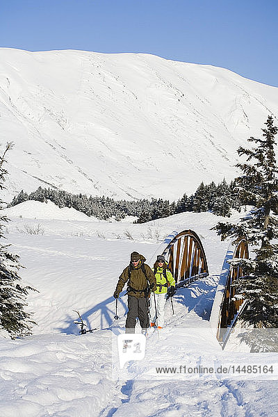 Two back country skiers ski across a bridge near the Turnagain Pass area of the Chugach National Forest. Winter on the Kenai Peninsula of Alaska.