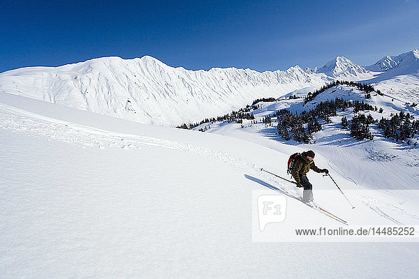 Man backcountry skiing down a mountain side in the Turnagain Pass area of the Chugach National Forest. Winter on the Kenai Peninsula of Southcentral Alaska.