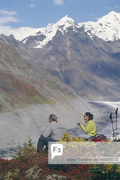 Backpackers take a break from climbing during a Fall trip at Wrangell-St.Elias National Pakr in Southcentral Alaska.