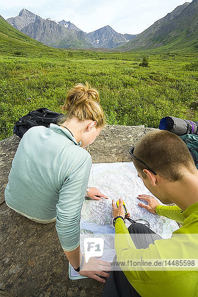 Male & female hikers looking at map while resting on rock in Chugach State Park Alaska Summer