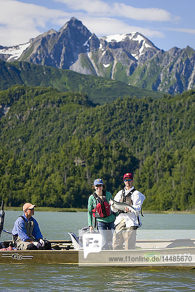 Man and woman stand in boat holding salmon catch of the day on Big River Lakes with fishing guide with the Chigmit Mountains in the background during Summer Southcentral Alaska