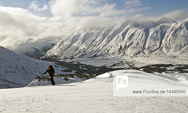 A backcountry skier skinning up a ridge in Turnagain Pass  Alaska
