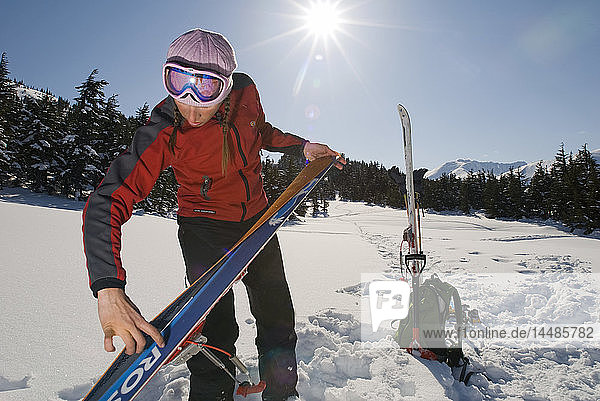 Woman prepares for backcountry skiing in Turnagain Pass of Southcentral Alaska during Winter