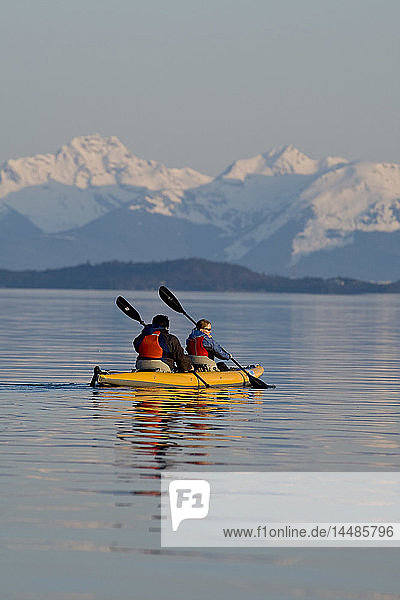 Sea Kayakers paddle the shoreline on a calm evening in Favorite Passage near Juneau  Alaska with Eagle Peak & Admiralty Island in the background