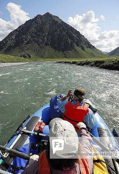 Two rafters rowing through a fast stretch of the Kongakut River on a sunny day with scenic mountains in the background  ANWR  Arctic Alaska  Summer