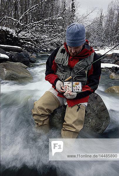 Flyfisherman Choosing Fly While Sitting in River SC AK