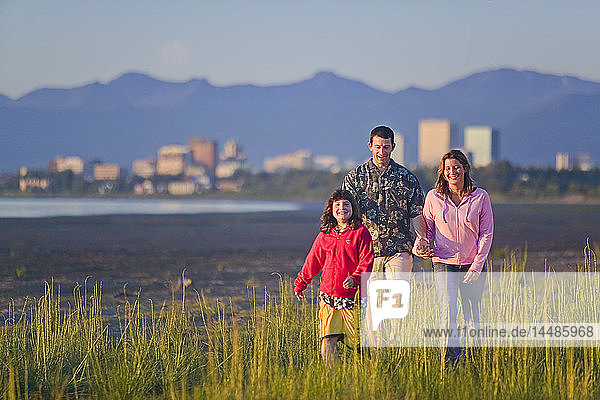 Family walking on beach along Turnagain Arm near Tony Knowles Coastal Trail Anchorage Alaska Summer SC