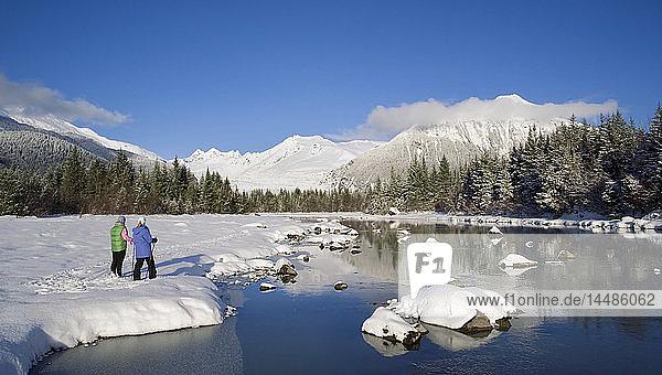 Mother & daughter cross-country skiing along Mendenhall River Alaska Winter Tongass Nat Forest