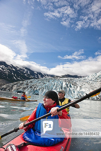 Kayaking couple paddling with Shoup Glacier behind them  Shoup Bay State Marine Park  Southcentral Alaska