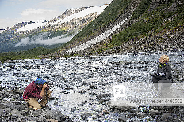 Man photographing a woman writing in her journal while sitting on a boulder in Portage Creek  Portage Valley  Southcentral Alaska