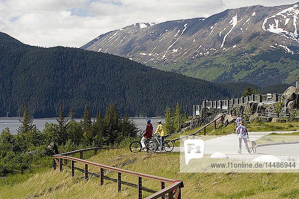 Young Couple Bikes on Path @ Bird Pt Rest Stop AK SC Turnagain Arm Chugach Mtns Summer