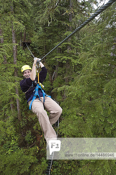 Female rides a zip line through the rainforest canopy near Ketchikan  Alaska