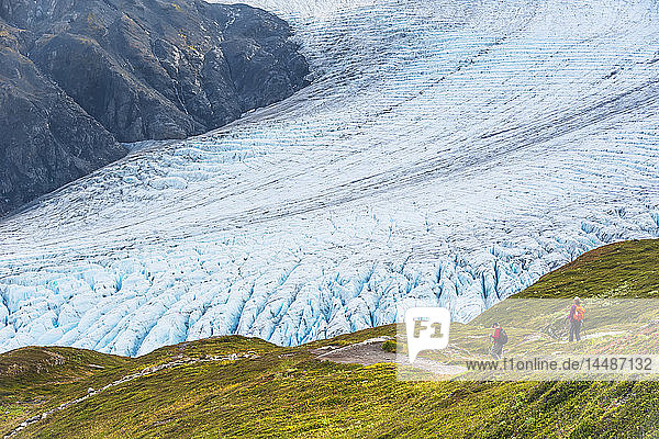 A man and woman hiking down the Harding Icefield Trail with Exit Glacier in the background  Kenai Fjords National Park  Kenai Penninsula  Southcentral Alaska