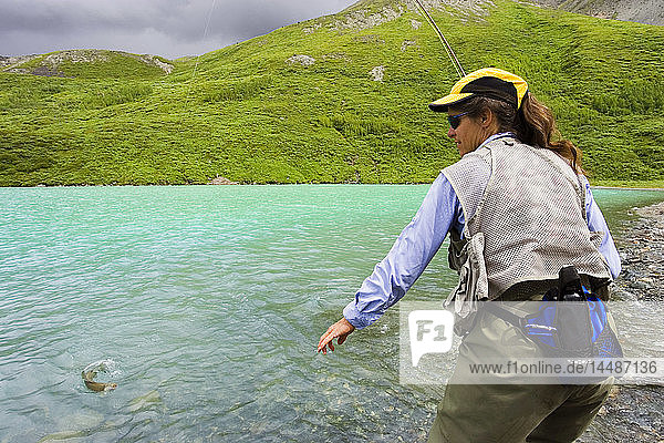 Woman flyfishing for arctic grayling from shore Turquoise Lake Lake Clark National Park Alaska Summer