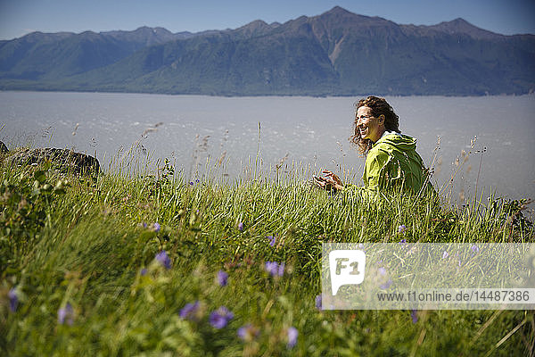Woman with a smart phone sitting amongst wildflower along Turnagain Arm  Kenai Mountains in the background  Southcentral alaska  Summer