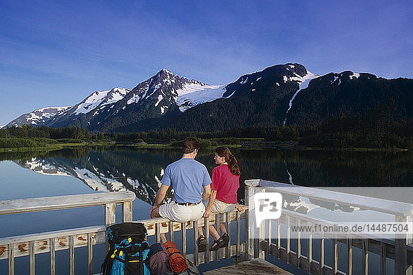 Couple Relaxes on Deck Moose Pond Portage Valley Southcentral Alaska Summer