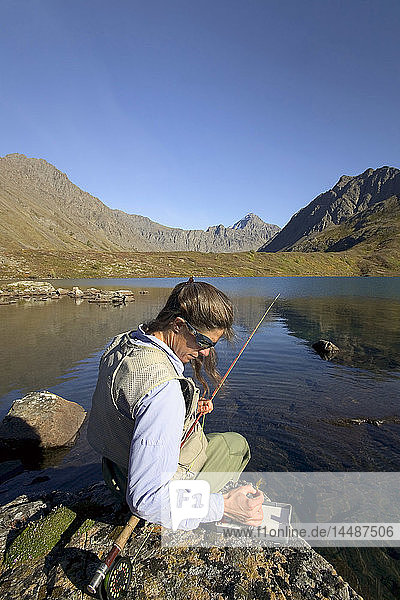 Flyfisherwoman sits on rock in Symphony Lake selecting fly from box Chugach State Park Alaska Autumn Remote