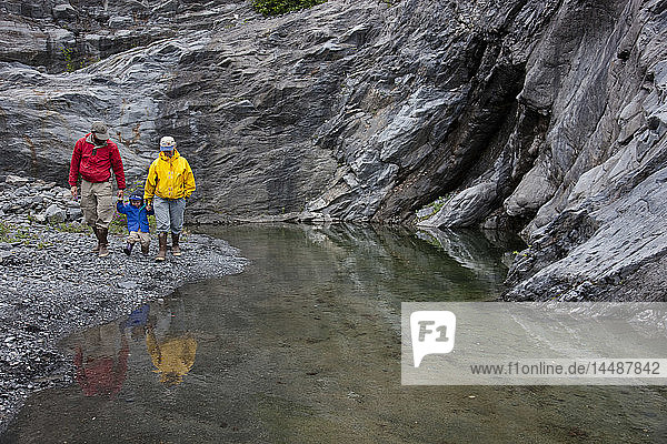 Family playing on the shores of a rocky pool carved out of the bedrock by Shoup glacier  Shoup Bay State Marine Park  Prince William Sound Southcentral Alaska