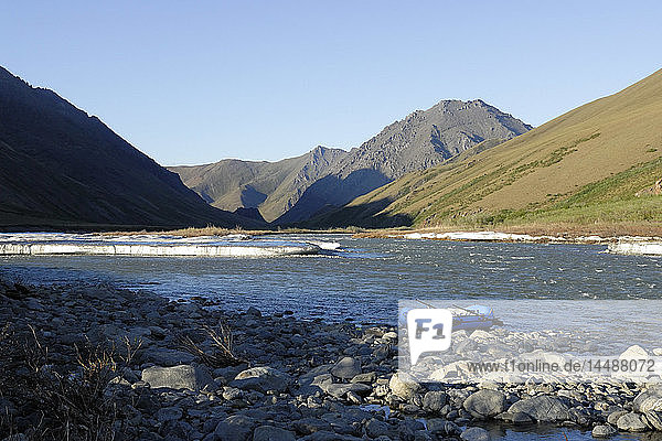Scenic view of a raft beached along the riverbank of Kongakut River with residual ice melting  ANWR  Arctic Alaska  Summer