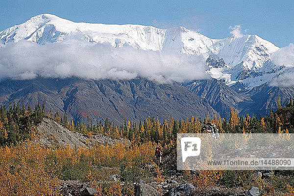 Pair of hikers enjoy the fall colors as they return from a week long backpacking trip into Wrangell-St.Elias National Park in Southcentral Alaska.