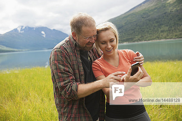 Man and Woman reviewing photos on a smartphone in front of Eklutna Lake  Chugach State Park  Southcentral Alaska