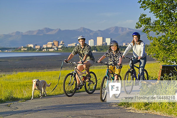Family w/pet companion riding bicycles on Tony Knowles Coastal Trail Anchorage Alaska Summer