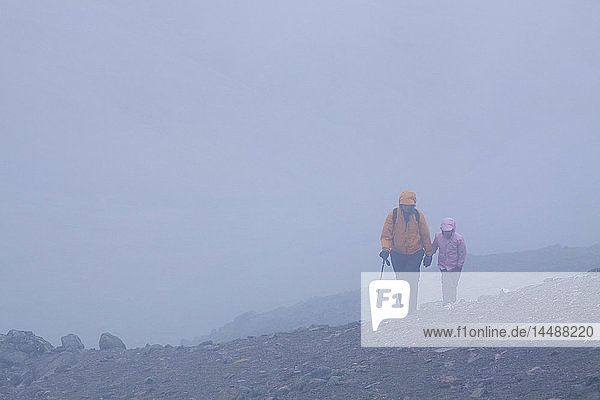 Mother and daughter hike on a talus slope in the rain and fog near Highway Pass  Alaska Range  Interior Alaska  Summer/n