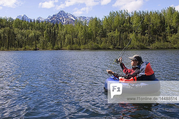 Fly fisherwoman in float tube casts for rainbow trout on Weiner Lake in Southcentral Alaska summer