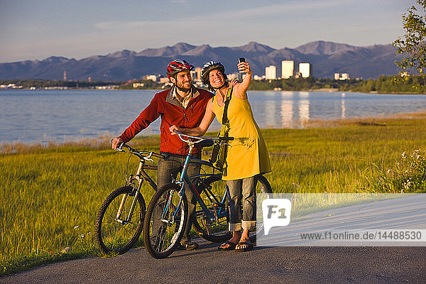 Bicyclists resting and taking self-portraits along the Tony Knowles Coastal Trail with the Anchorage skyline in the background  Southcentral Alaska