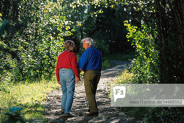 Family walks down trail in forest Anchorage SC Alaska some w/fishing pole or bbBat