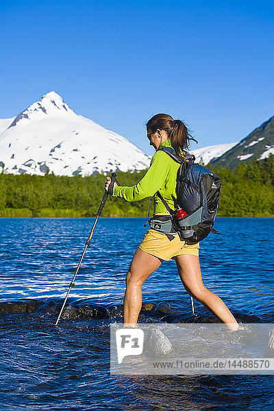 Female hiker crossing stream in Portage Valley of the Chugach National Forest in Southcentral Alaska during Summer