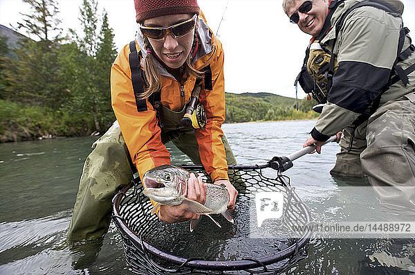 Man and Woman hold a rainbow trout caught while fly fishing on the upper Kenai River on the Kenai Peninsula of Southcentral Alaska during Fall