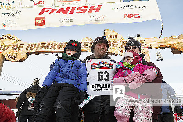 Aaron Burmeister poses with his family shortly after finishing in third place at in Nome during Iditarod 2015