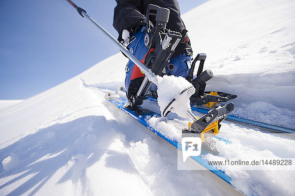 Close up of a backcountry skiers ski and boot in motion on a trek towards Tincan Ridge in the Turnagain Pass area of Southcentral Alaska during Winter