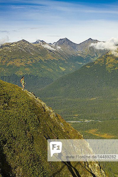 Young adult Hispanic woman hiking on top of Mt. Alyeska with view of Chugach Mountains & Girdwood Valley in Southcentral Alaska
