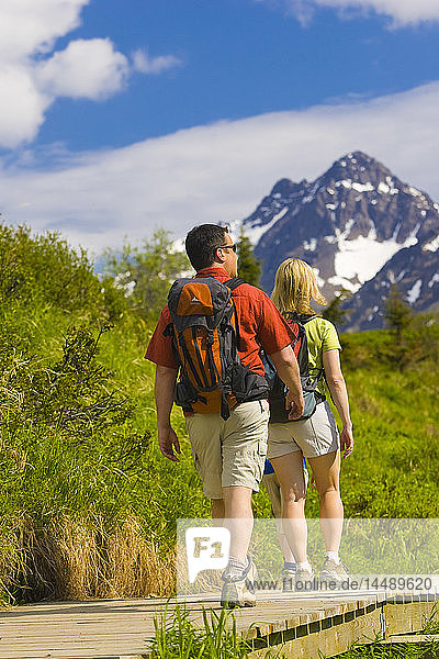 Couple hiking on the boardwalk of the Middle Fork Loop Trail in the Glen Alps area of Chugach State Park  southcentral Alaska