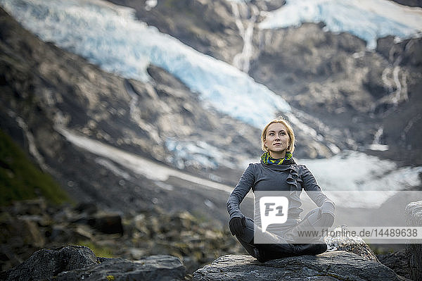 Woman sits on a boulder in a yoga pose with Byron Glacier in the background  Portage Valley  Southcentral Alaska