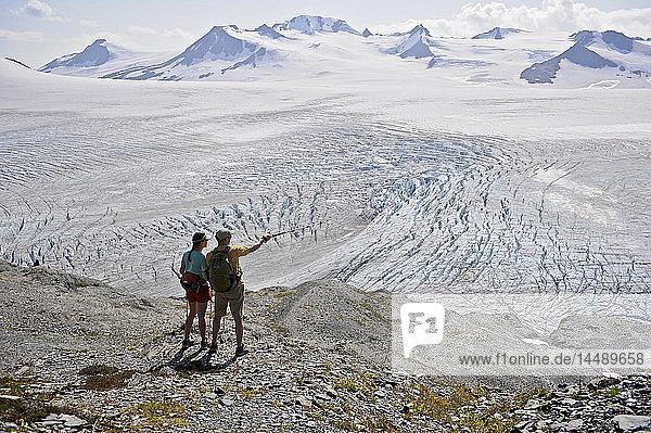 Man and woman enjoy view overlooking Harding Icefield  Kenai Fjords National Park  Kenai Peninsula  Southcentral Alaska  Summer