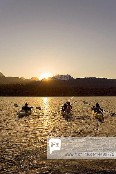 Family sea kayaking in together into sunset on Bear Lake Kenai Peninsula Alaska Summer