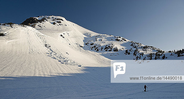 A backcountry skier skinning beneath chunks of a cornice that caused a small avalanche near Juneau  Alaska