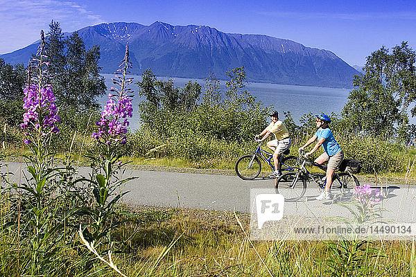 Couple riding bikes together on Coastal Trail near Indian Alaska Turnagain Arm  SC Summer.