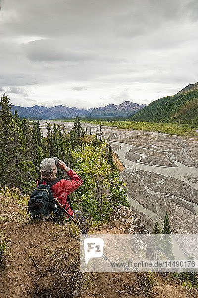 Female hiker stops to view the Teklanika River and Alaska Range near the Teklanika Campground  Denali National Park  Interior Alaska  Summer