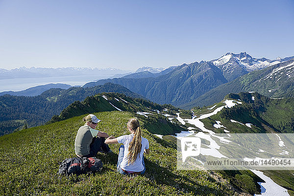 Hikers rest and admire the view in the alpine above Amalga Basin in the Tongass Forest  near Juneau  Alaska.
